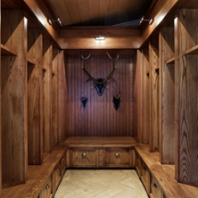 A wide shot of a fully panelled custom joinery mudroom with deer antlers on the far wall.